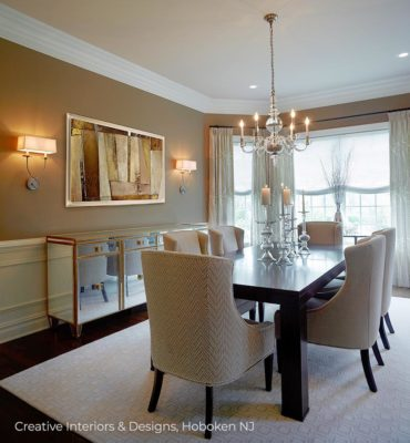 A formal dining room design with exquisite modern chandelier and mirrored credenza.
