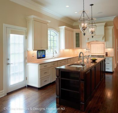 White kitchen cabinets contrast with dark wood island, elegant candle pendant lighting.
