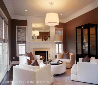 Luxurious living room design has white chairs and ottoman, white fireplace offset by dark brown wall color.