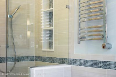 Large grey porcelain shower tile with blue accent tiles in this bathroom remodel shower.