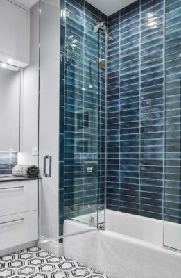 In this bathroom remodel the shower has blue ceramic subway tile.
