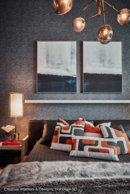 Faux fur blanket and colorful geometric pattern pillows in modern bedroom interior design.
