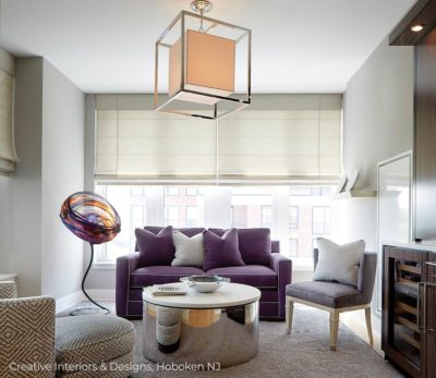 Square chandelier pendant lighting and purple accent loveseat sofa in a small sitting room.