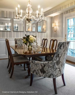 Modern Transitional dining room has thick grey striped wallpaper and extraordinary Mid Century style modern chandelier.
