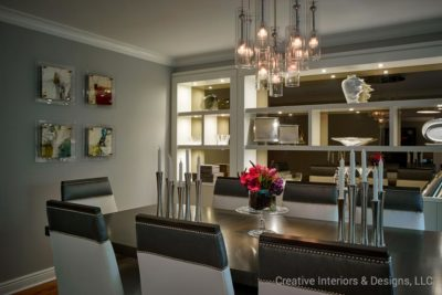 Grey studded upholstered dining room chairs with silver candle holders in this luxurious modern dining room.