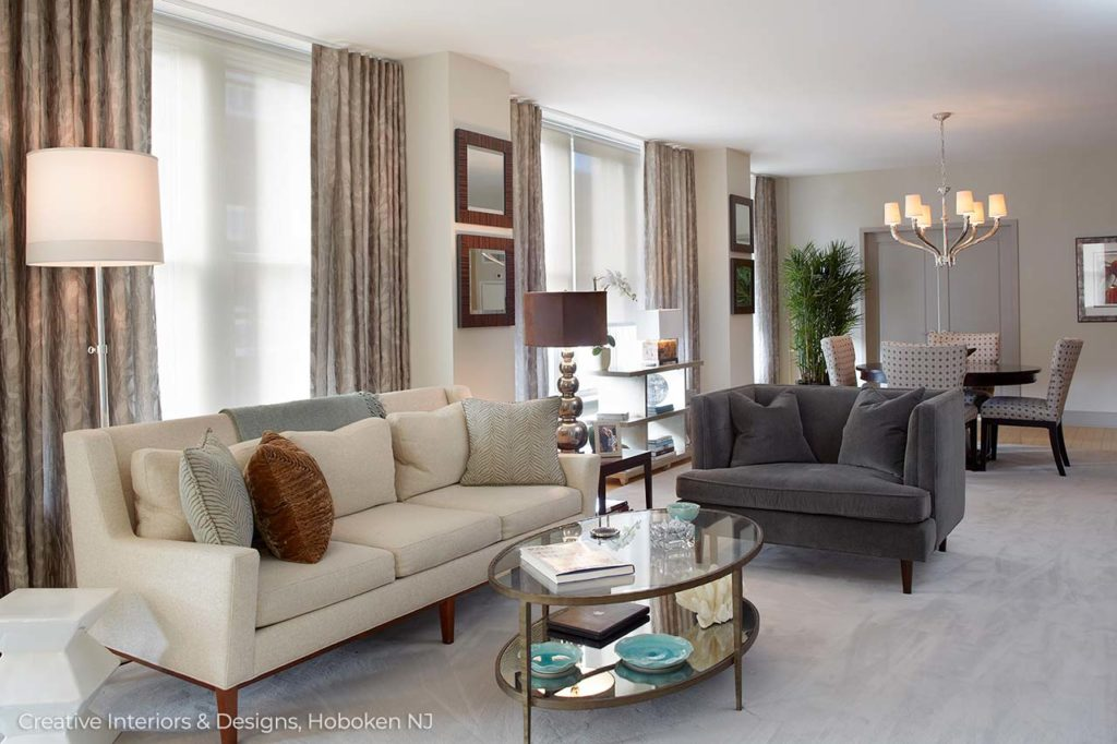 This spacious living room has a  clean sophisticated look with neutral tones and a sleek mid century modern grey sofa.