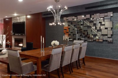 Modern chandelier is reflected in a large multi faceted decorative wall mirror displayed on grey textured wallpaper in this open space apartment.