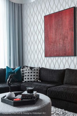 Luxurious black sectional, modern wall art and teal accent throw pillow.