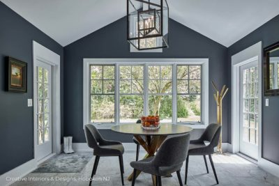 A lantern pendant light in this small casual dining area with navy accent walls.
