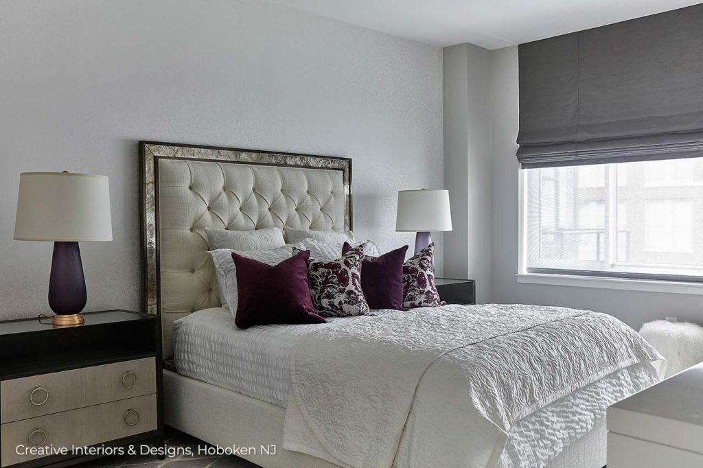 Modern grey bedroom with an upholstered headboard and mid century nightstand.