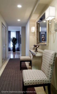 Elegant square shade glass sconces and geometric pattern chair in this modern hallway.