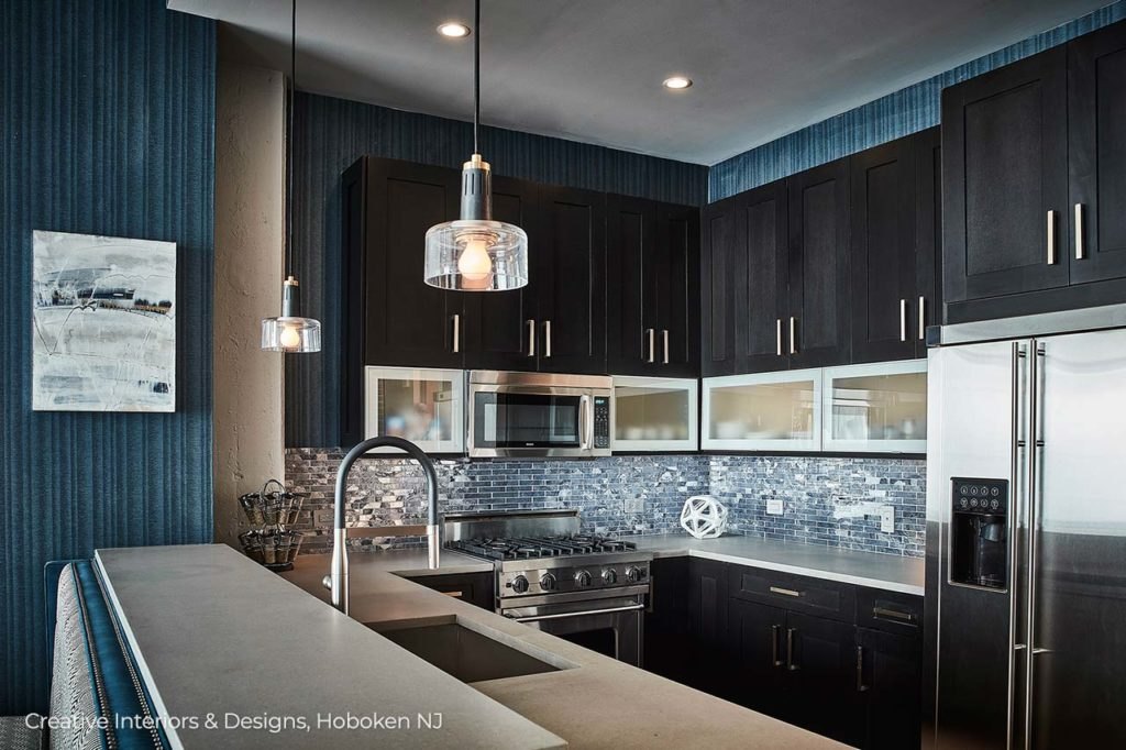 A modern kitchen remodel features black cabinets and blue glass subway tile backsplash.