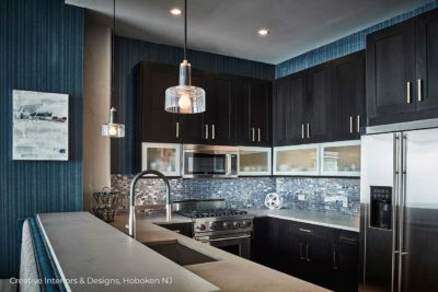 Dramatic black kitchen cabinets with blue glass subway tile backsplash.
