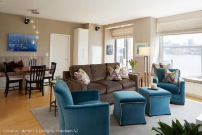 Teal mid century chairs accent this modern living room design with comfortable brown sofa.