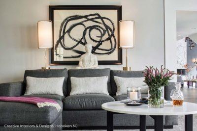 Modern wall art and buddha statue home decor over a comfortable grey sectional sofa.