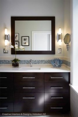 Modern black and white bathroom renovation with expresso vanity, black mirror and blue accent tile.