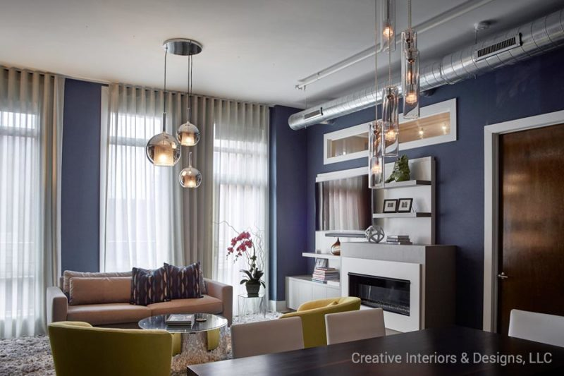 Navy blue accent wall and mid century pendant lighting in this Urban Modern living room design.