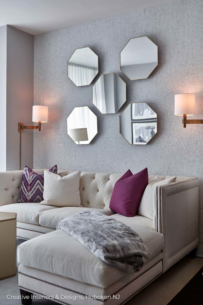 Modern interior decoration has white sectional sofa with chaise and raspberry throw pillows accent.