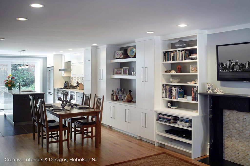 Open concept kitchen and dining room with built in white shelves.