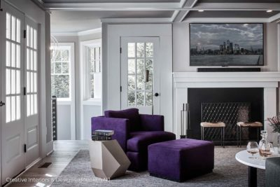 Comfortable oversized purple accent chair with ottoman in this modern grey living room design.