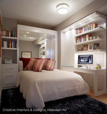 Small bedroom has built in bookshelf desk and a large wall mirror headboard.